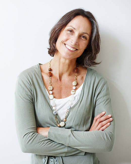 Mature middle aged woman with her arms crossed against white, smiling