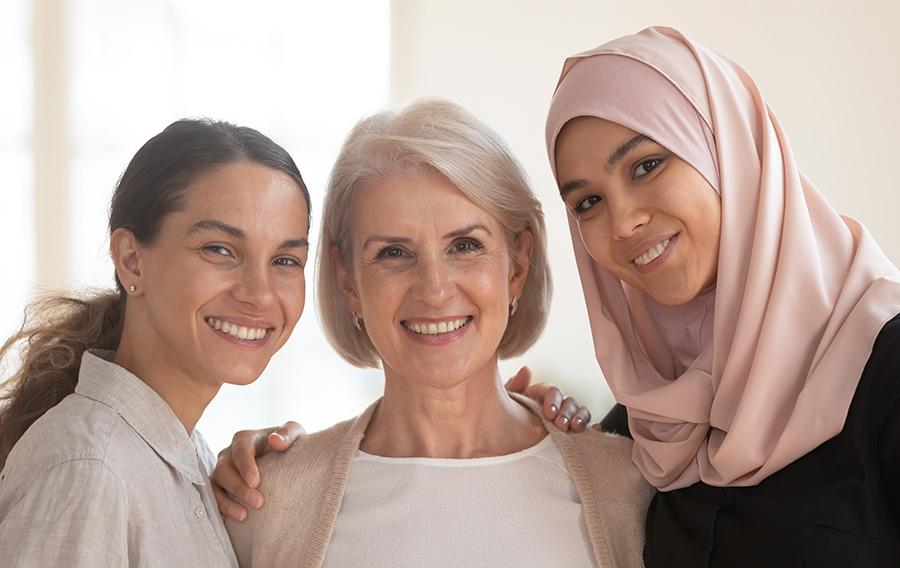 Three beautiful diverse women, two generation, bonding looking at camera